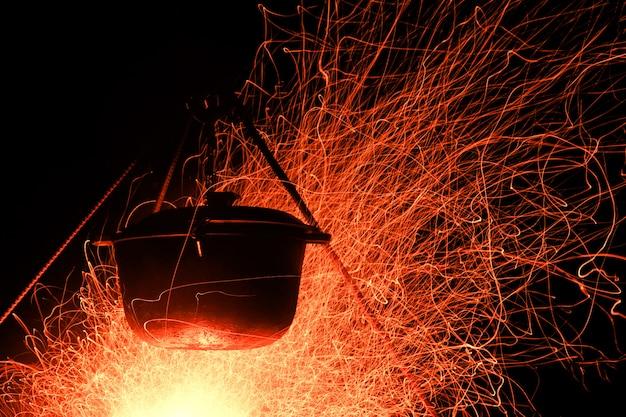 Cuisiner sur le bûcher la nuit. grosse flamme
