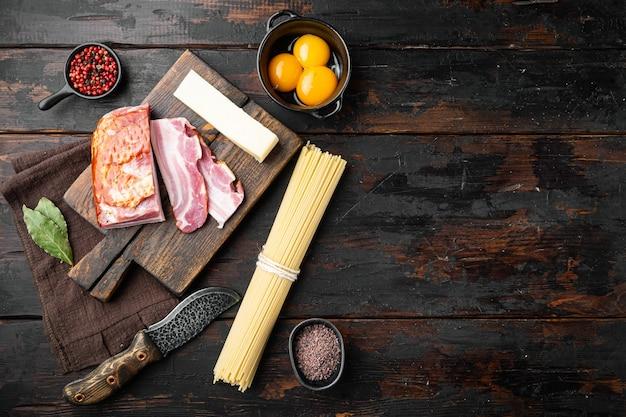 Cuisiner le collage de la cuisine italienne. ingrédients pour pâtes carbonara, spaghettis, huile, jambon, oeuf et parmesan, sur la vieille table en bois sombre, vue de dessus à plat, avec espace de copie