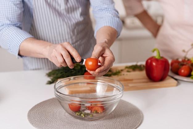 Cuisiner un dîner végétarien. homme d'âge mûr capable qualifié debout dans la cuisine et la cuisson de la salade végétarienne tandis que sa mère senior le regarde