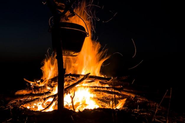 Cuisiner sur le feu pour une virée en camping marmite au-dessus d'un feu en plein air le romantisme du tourisme sauvage et...