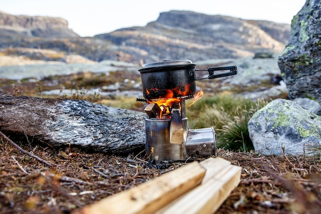 Cuisiner sur un petit réchaud de camping dans un camp de montagne.