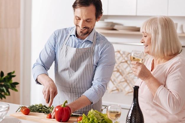 Cuisiner pour ma mère. cheerful smiling mature fils debout dans la cuisine et la cuisson de la salade végétarienne tandis que sa mère âgée de boire du vin