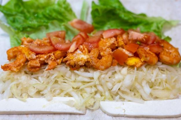 Cuisiner un rouleau de restauration rapide fait maison en gros plan. chou, crevettes frites et tomates avec du fromage sur du pain pita. une collation copieuse rapide et délicieuse pour l'école ou le travail