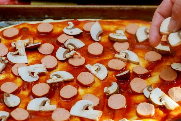 Cuisinez dans la cuisine en mettant les ingrédients sur la pizza préparée
