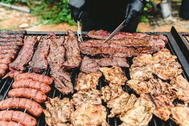Cuisinez en préparant de la viande grillée lors d'un barbecue.