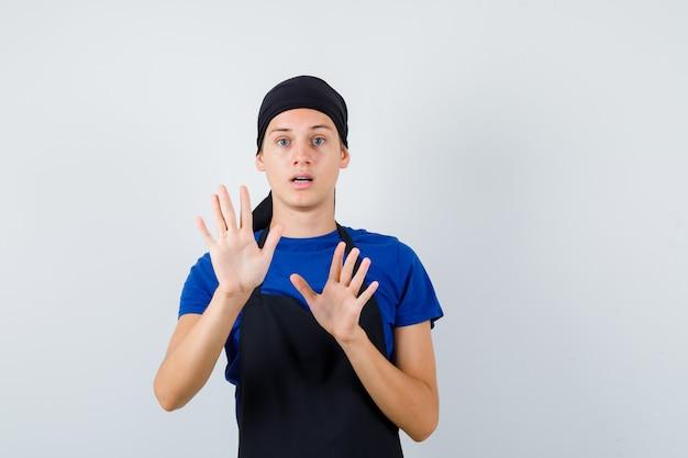 Cuisinier adolescent masculin levant la main pour se défendre en t-shirt, tablier et ayant l'air effrayé. vue de face.