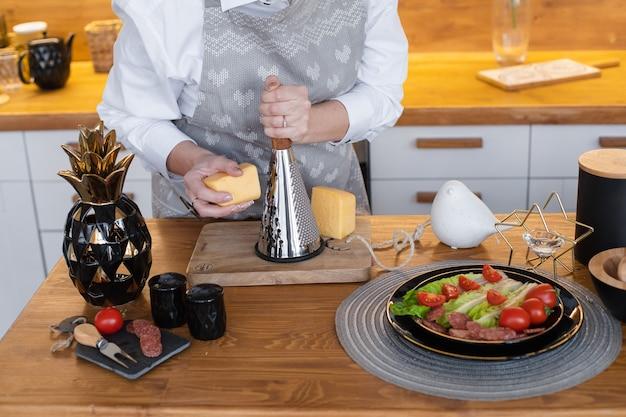 Le cuisinier caucasien frotte le fromage pour différents plats sur la table