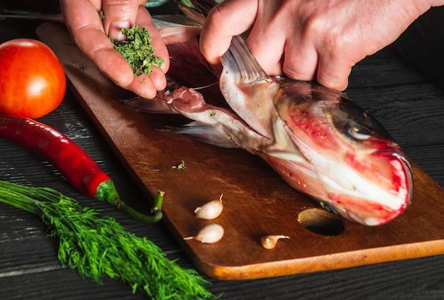 Le cuisinier ou le chef prépare la carpe à grosse tête de poisson frais avec du piquant. préparation à la cuisson des aliments pour poissons. environnement de travail dans la cuisine du restaurant ou du café