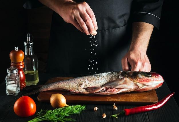 Le cuisinier ou le chef prépare la carpe à grosse tête de poisson frais en saupoudrant de sel avec les ingrédients. préparation à la cuisson des aliments pour poissons. environnement de travail dans la cuisine du restaurant
