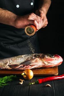 Le cuisinier ou le chef prépare du poisson frais carpe à grosse tête en saupoudrant de poivre. préparation à la cuisson des aliments pour poissons. environnement de travail dans la cuisine du restaurant ou du café