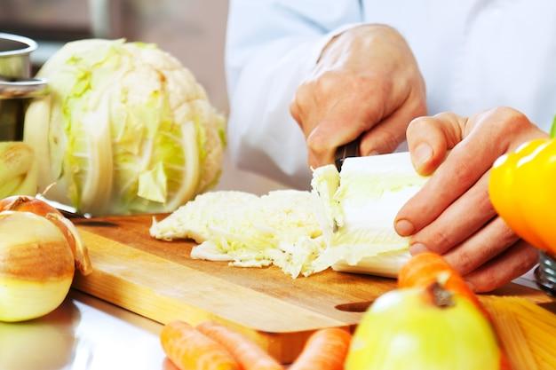 Cuisinier coupe la laitue avec un couteau