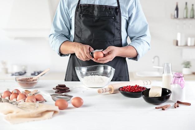 Un cuisinier dans une cuisine rustique. les mains mâles avec des ingrédients pour la cuisson de produits à base de farine ou de pâte, pain, muffins, tarte, gâteau, pizza