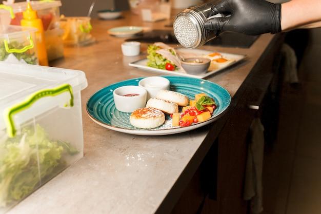 Le cuisinier du restaurant a préparé de délicieuses crêpes au fromage et les saupoudre de poudre