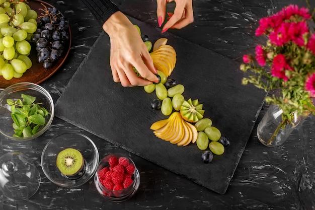 Le cuisinier enseigne un dessert aux fruits.