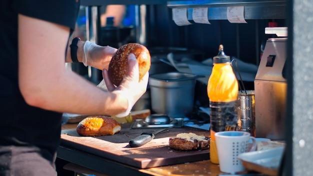 Un cuisinier fait un hamburger avec plusieurs ingrédients, bbq