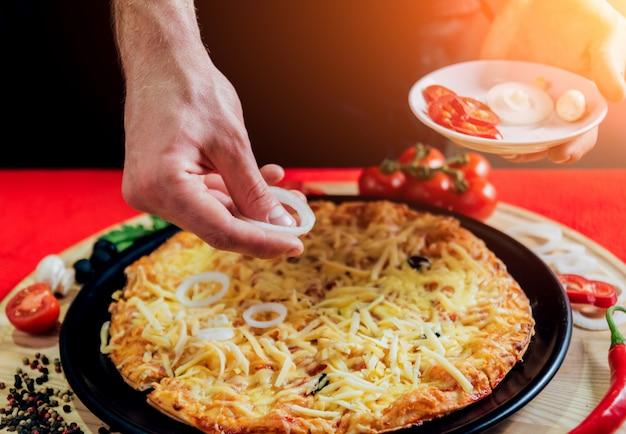 Le cuisinier fait de la pizza. ajoute les ingrédients.