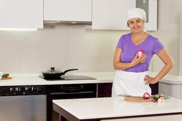 Cuisinier féminin debout fier avec la main sur la taille dans la cuisine
