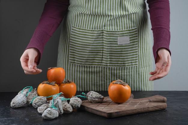 Cuisinier féminin essayant de choisir les kakis frais ou secs sur la table noire