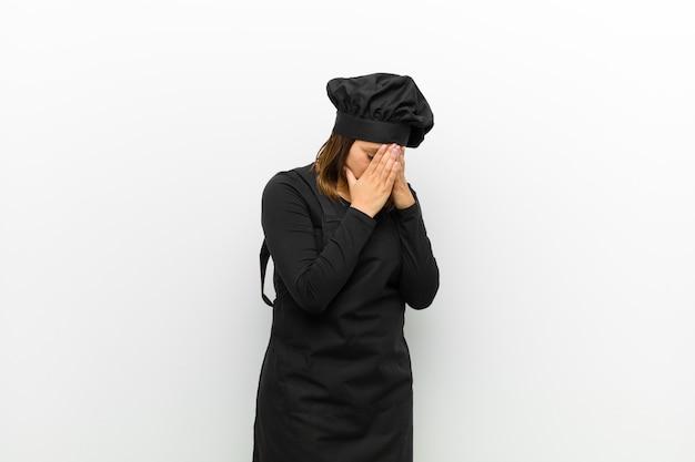 Cuisinier femme couvrant les yeux avec les mains avec un regard triste et frustré de désespoir, pleurer, vue de côté