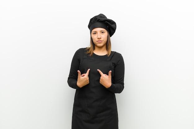 Cuisinier femme pointant sur soi avec un regard confus et interrogatif, choqué et surpris d'être choisi