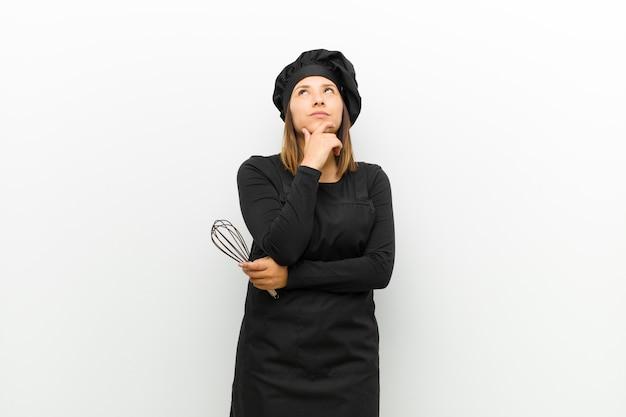 Cuisinier femme se sentant réfléchie, se demandant ou imaginant des idées, rêvassant et levant les yeux pour copier l'espace