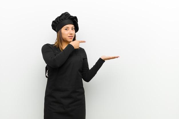 Cuisinier femme souriant joyeusement et pointant vers la surface sur la paume sur le côté, montrant ou annonçant un objet contre le blanc