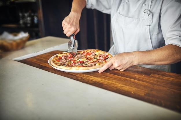 Le cuisinier garde une grosse pizza.