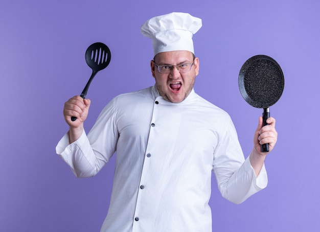 Cuisinier mâle adulte furieux portant un uniforme de chef et des lunettes montrant une cuillère à fentes et une poêle à frire à l'avant en regardant devant crier isolé sur un mur violet