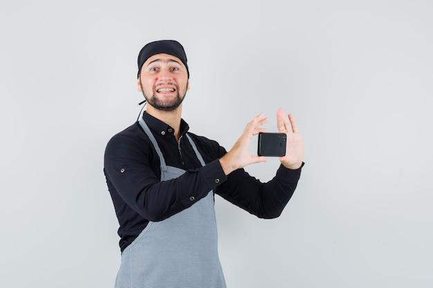 Cuisinier mâle prenant photo sur téléphone mobile en chemise, tablier et à la joyeuse. vue de face.