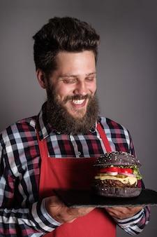 Cuisinier masculin en tablier rouge vous donnant un hamburger noir frais et souriant