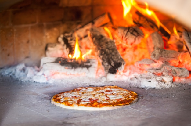 Cuisinier préparant une pizza dans un restaurant.