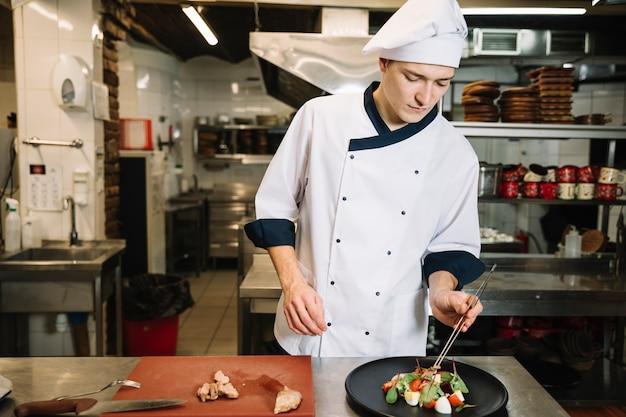 Cuisinier préparant une salade avec de la viande à table