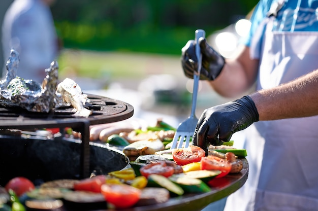 Le cuisinier prépare les légumes et la viande sur le gril en été