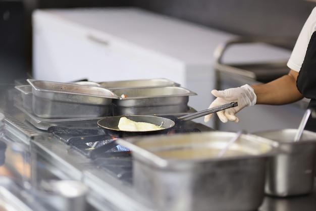 Le cuisinier prépare l'omelette dans la poêle dans le plan rapproché de cuisine