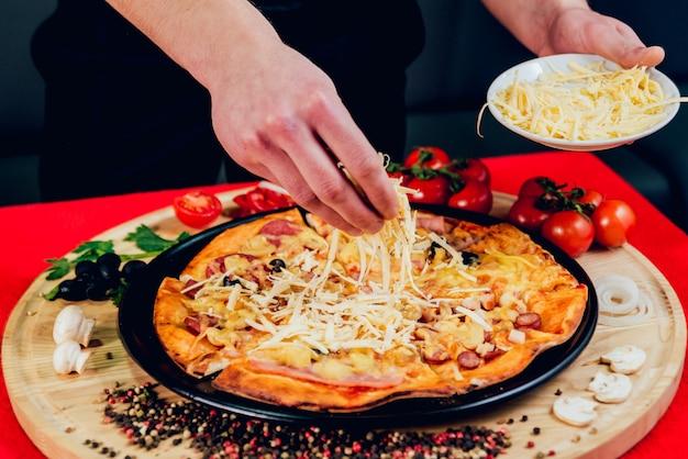 Le cuisinier prépare une pizza. ajoute les ingrédients.
