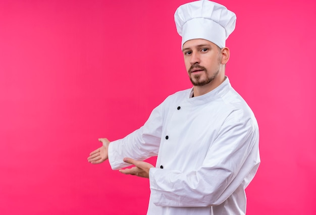 Cuisinier professionnel masculin en uniforme blanc et chapeau de cuisinier présentant l'espace de copie avec les bras de ses mains debout sur fond rose