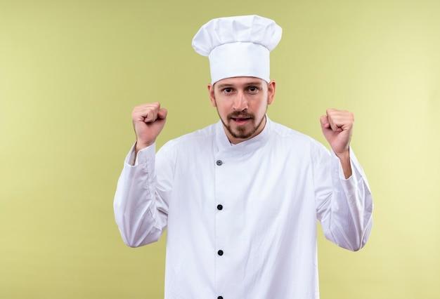 Cuisinier professionnel masculin en uniforme blanc et chapeau de cuisinier serrant les poings heureux et excité se réjouissant de son succès debout sur fond vert