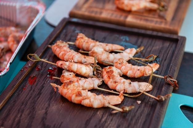 Un cuisinier professionnel prépare des crevettes sur le grill extérieur, concept alimentaire ou traiteur