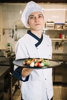 Cuisinier tenant une salade de viande sur une grande assiette