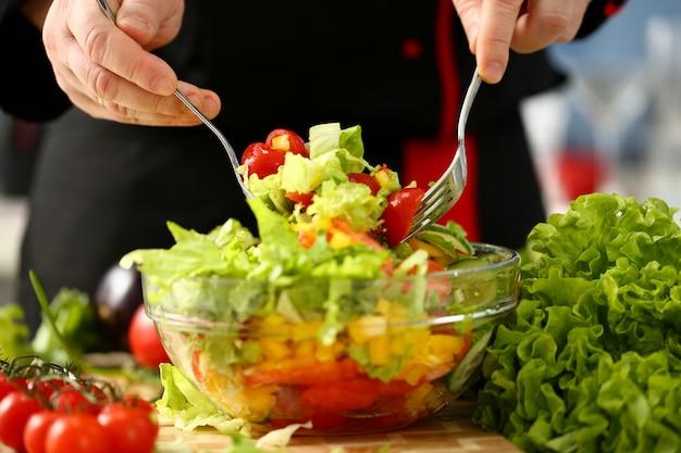 Cuisinier tient la fourchette à la main et mélange