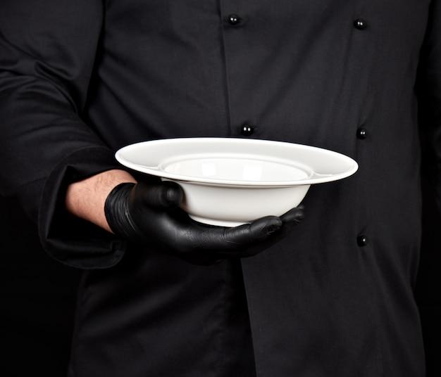 Cuisinier en uniforme noir et gants en latex noir tient dans sa main une assiette blanche vide ronde