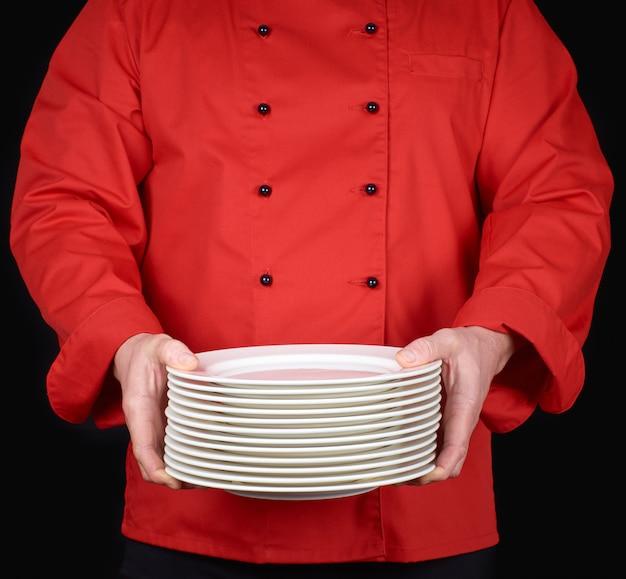 Cuisinier en uniforme rouge tient dans ses mains une pile d'assiettes rondes vides blanches, noires
