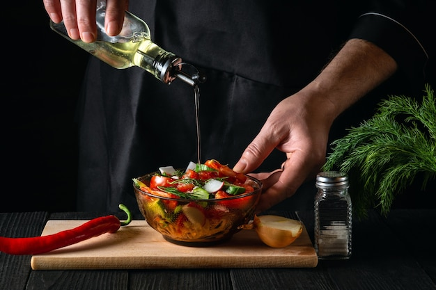 Le cuisinier verse l'huile d'olive dans un bol de salade