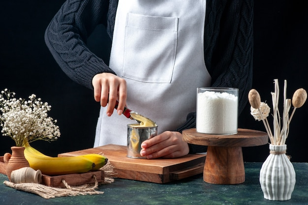 Cuisinier vue de face essayant d'ouvrir la boîte avec du lait concentré sur fond sombre