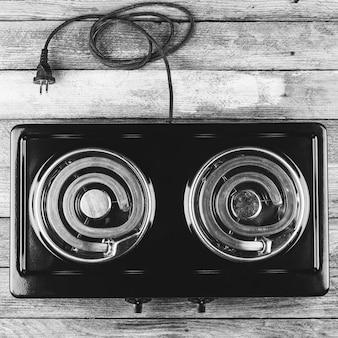 Cuisinière électrique avec deux fourchettes électriques sur une table en bois, gros plan vue de dessus, photo noir et blanc