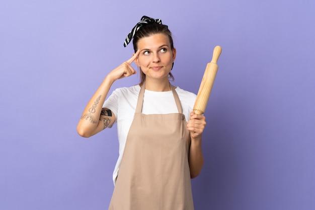 Cuisinière femme slovaque isolée sur fond violet ayant des doutes et pensant