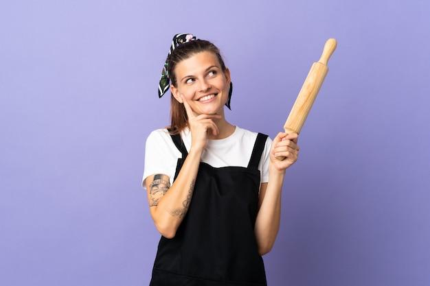 Cuisinière femme slovaque isolée sur fond violet en pensant à une idée tout en levant les yeux