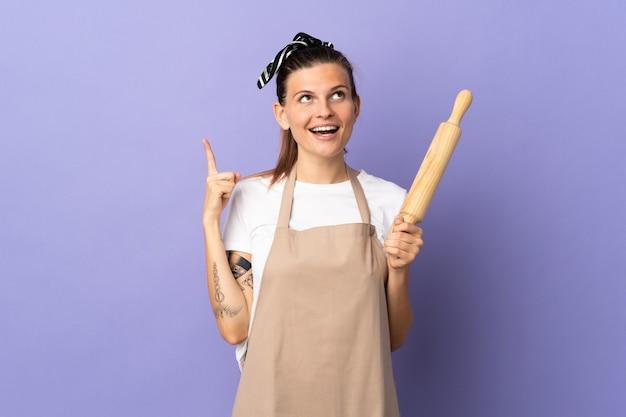 Cuisinière femme slovaque isolée sur fond violet pointant vers le haut et surpris