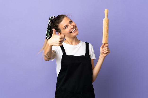Cuisinière femme slovaque isolée sur fond violet avec les pouces vers le haut parce que quelque chose de bien s'est produit
