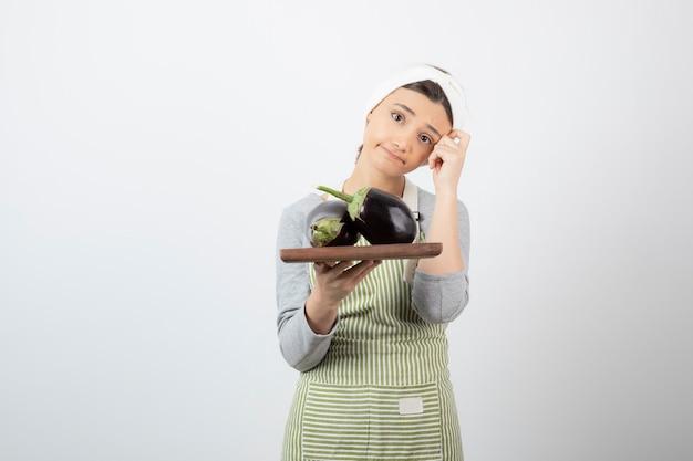 Cuisinière tenant une assiette de grosses aubergines et pensant.